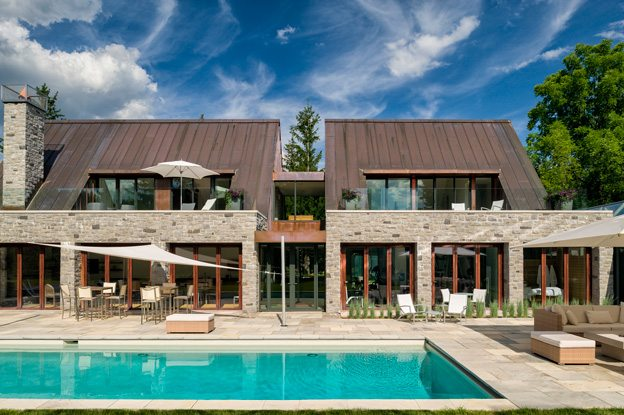 """Facing out over the pool, the second level of each building houses a compact guest suite with a sunny terrace. In the building to the left, a kitchen with a fireplace functions like a covered porch, the doors folding back to allow access to the patio. In the building to the right, there is a workout area and a spa room. The stonework and copper roofs complement the original home but don't mimic it. """"We wanted to give the sense that the owner 'found' these outbuildings and renovated them into what you see now,"""" says Hobin. Photo by Doublespace Photography."""