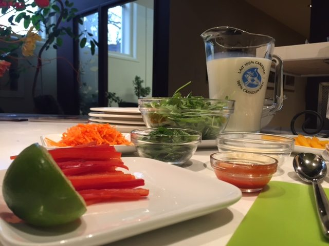 The mango and quinoa wraps feature several fresh ingredients, including mint leaves, coarsely grated carrot, a small red bell pepper, baby arugula leaves, and a small ripe but firm avocado.