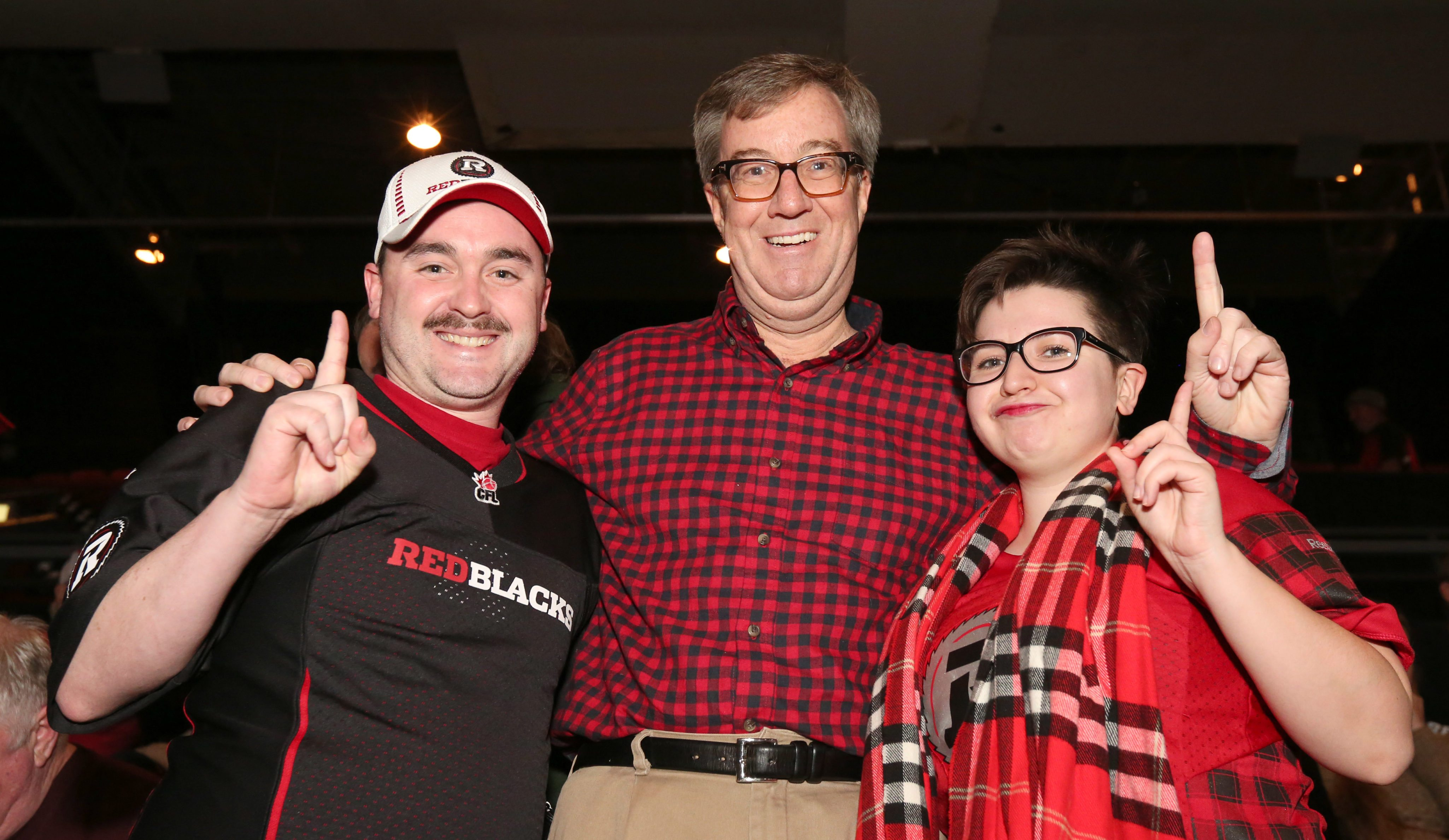 Walter Logue, left, Ottawa Mayor Jim Watson, centre, and Rosemary CotŽ, right, cheer prior to the start of the 103rd Grey Cup game between the Edmonton Eskimos and the Ottawa Redblacks at a viewing party at The Arena at TD Place. Photo by Jana Chytilova, OTTAWA magazine.