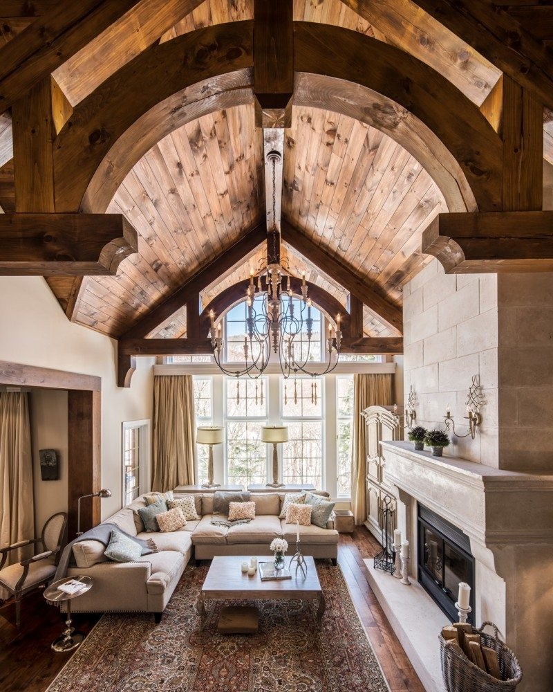 : When Crawford sketched out the dramatic ceiling in the great room, he envisaged the grandeur of a Baroque-era hall in England. The massive 200-year-old reclaimed wood beams were installed by a local craftsman skilled in building log homes. The rustic river-rock fireplace surround was replaced with a more classic look highlighting pale grey Italian limestone. Photo: Christiane Lalonde, Photolux Studio