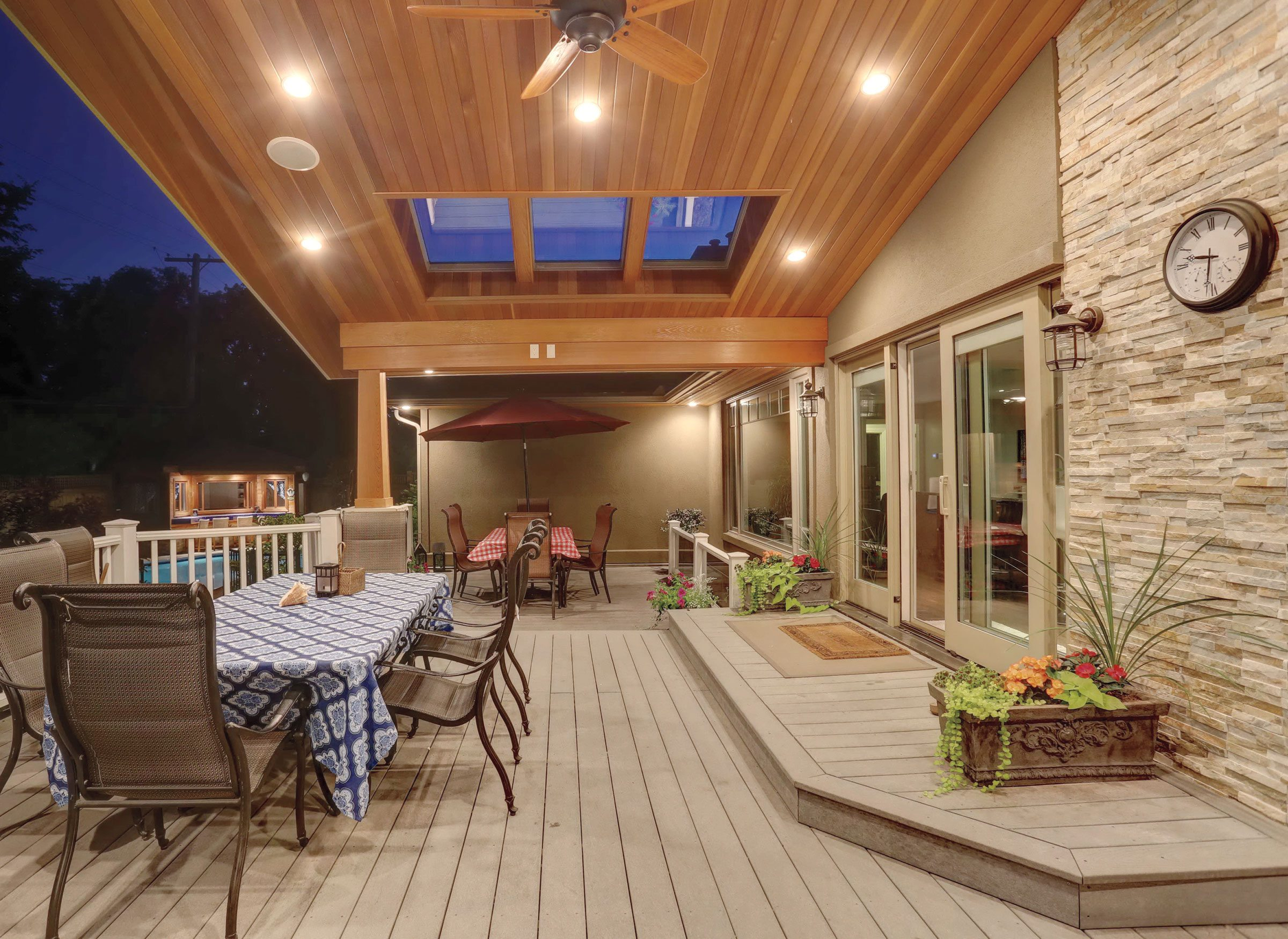 Because the deck faces west, the cedar canopy ensures it doesn't get too hot in the afternoon, while skylights allow light to filter in throughout the day. The seating area with the red sunshade is open to the elements. Stairs lead to a garden and pool