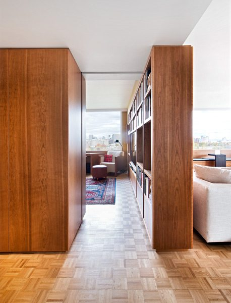On one side, the cherrywood divider forms an extended bookshelf in the home office. The back side is a floor-to-ceiling partition wall in the living room
