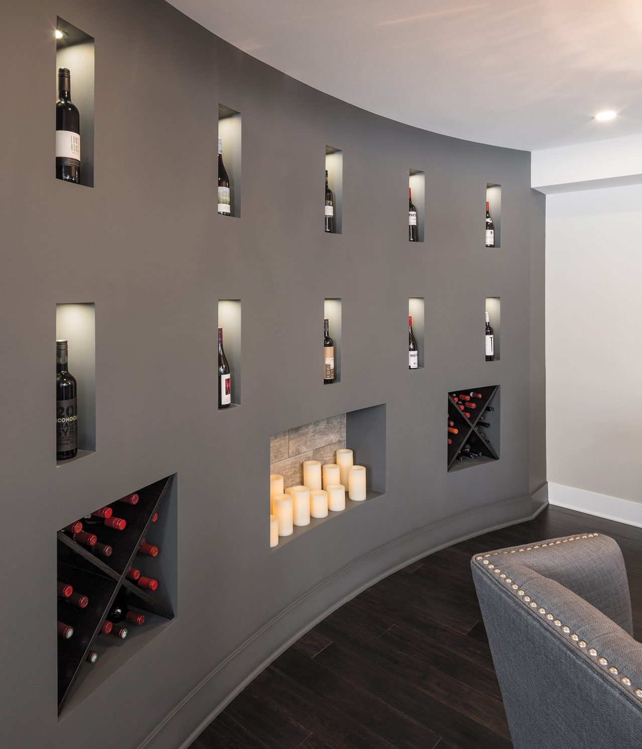 Ten identical niches are lit with LED lights so as not to overheat the wine. The grey palette, in concert with the wood-grained tile in the niches, reminds the owners of Tuscany. Photo: Justin Van Leeuwen