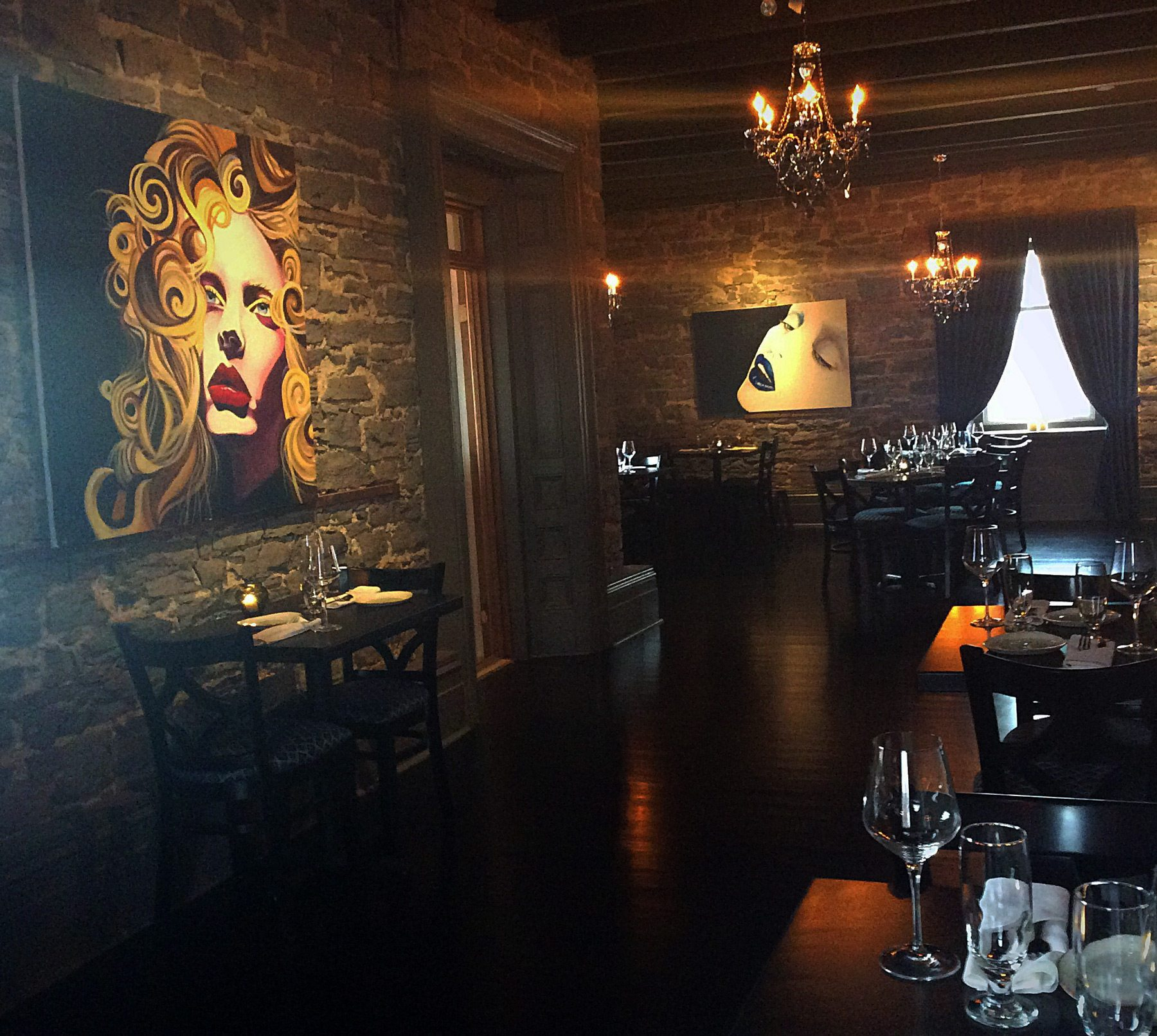 Original stone walls, pretty chandeliers, and commissioned pop-art portraits make for a unique dining space at La Maison Conroy