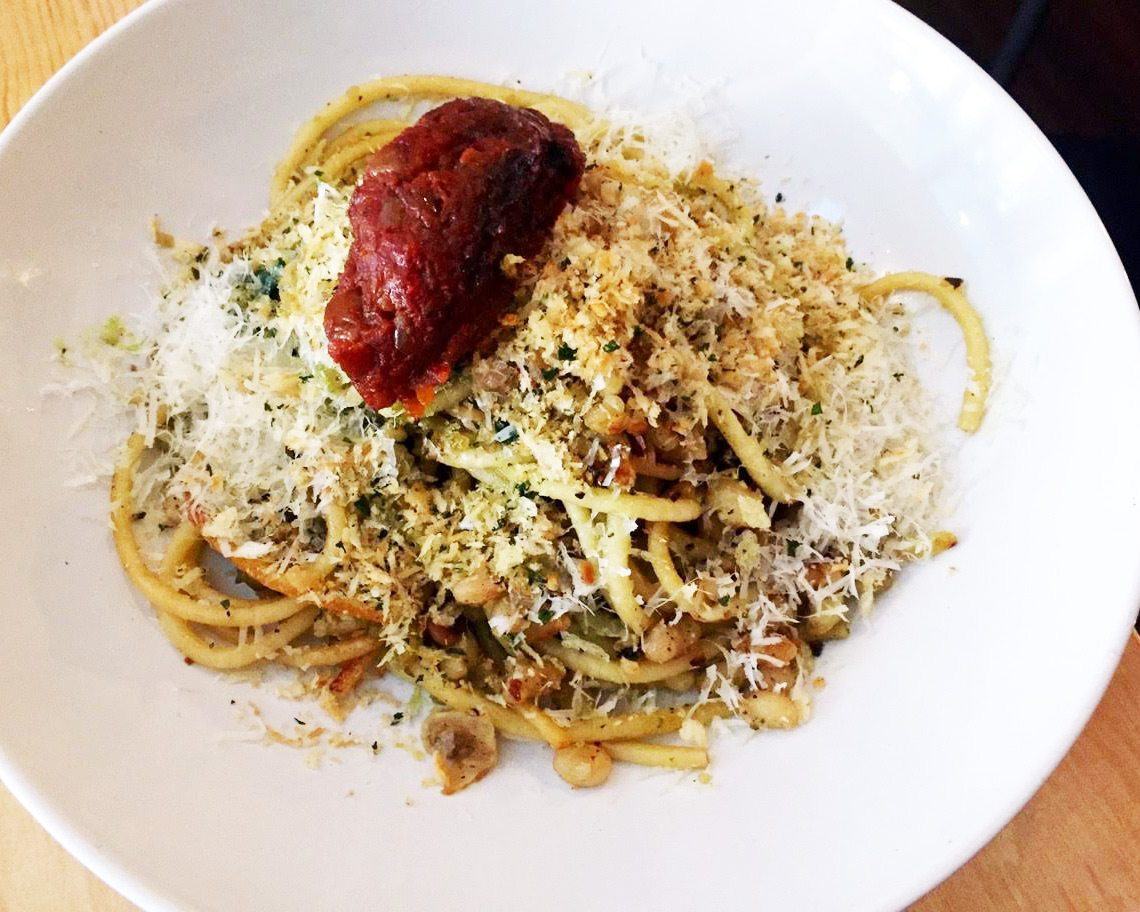 Perfectly chewy bucatini with a dark, deep tomato compote, crunchy-herby breadcrumbs, navy beans, wisps of softened kale, and loads of parmesan
