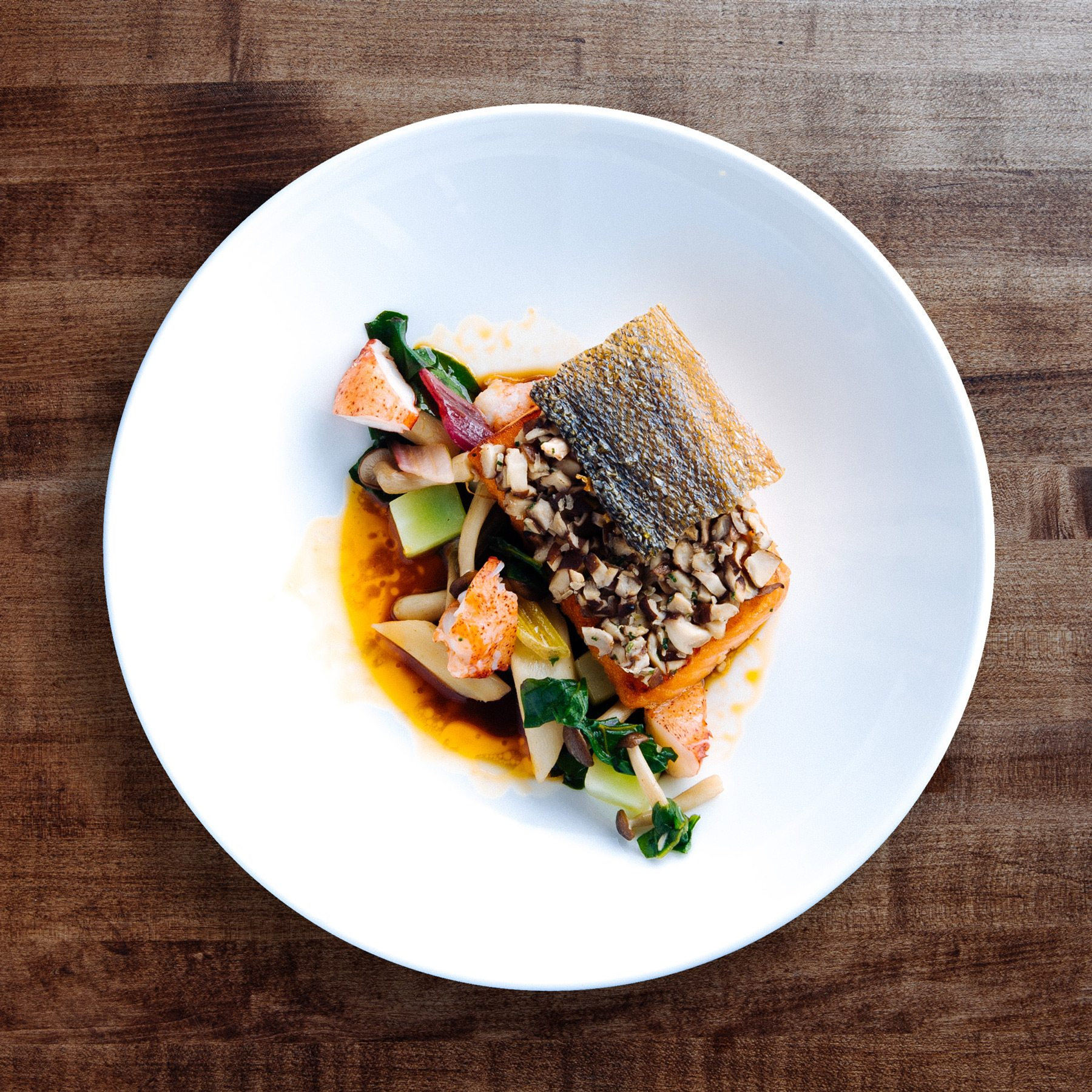 Mains on the seasonal menu include this organic salmon dish with mushroom duxelle and a honey lobster broth. Photo: Frazer Nagy of Transparent Kitchen