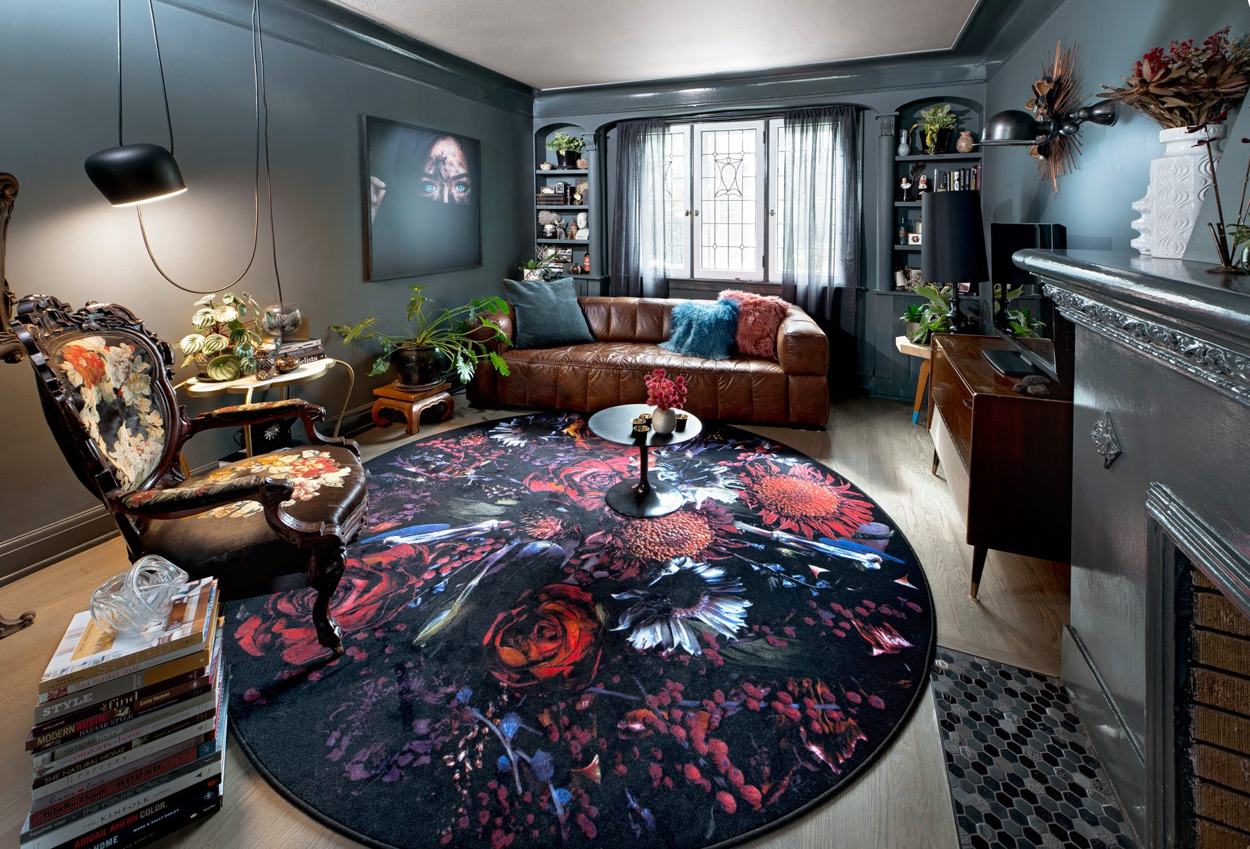 Every piece in the living room is unpredictable, making for a kind of exhibit of eras. The large photo on the wall is by a young photographer from Bali, while the side and end tables have been rebuilt by Jeff. A more modern find is the floral carpet by Moooi. Photography: Marc Fowler / Metropolis Studio