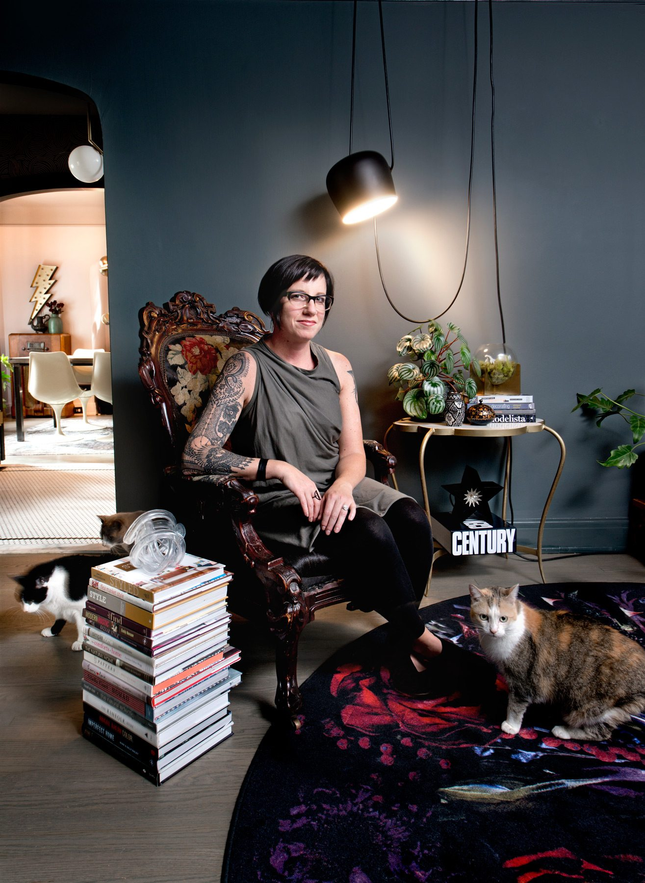 Kim poses with one of the resident felines in the living room, where a stack of hardcover design books serves as a side table. The pendant light above her head is by FLOS. Photography: Marc Fowler / Metropolis Studio