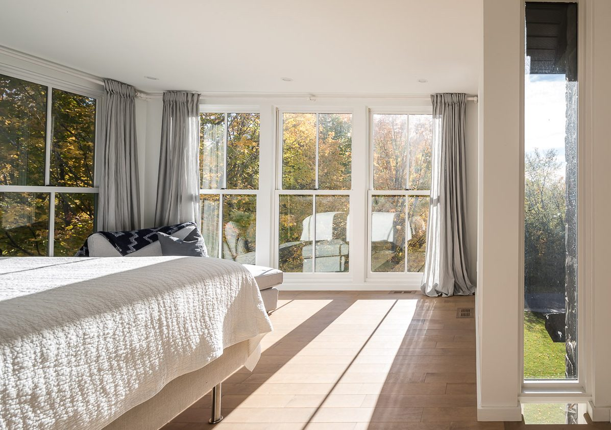 The master bedroom, located above the sitting room, boasts stellar views that take in the farmland beside the Mississippi River. Photography: Doublespace Photography