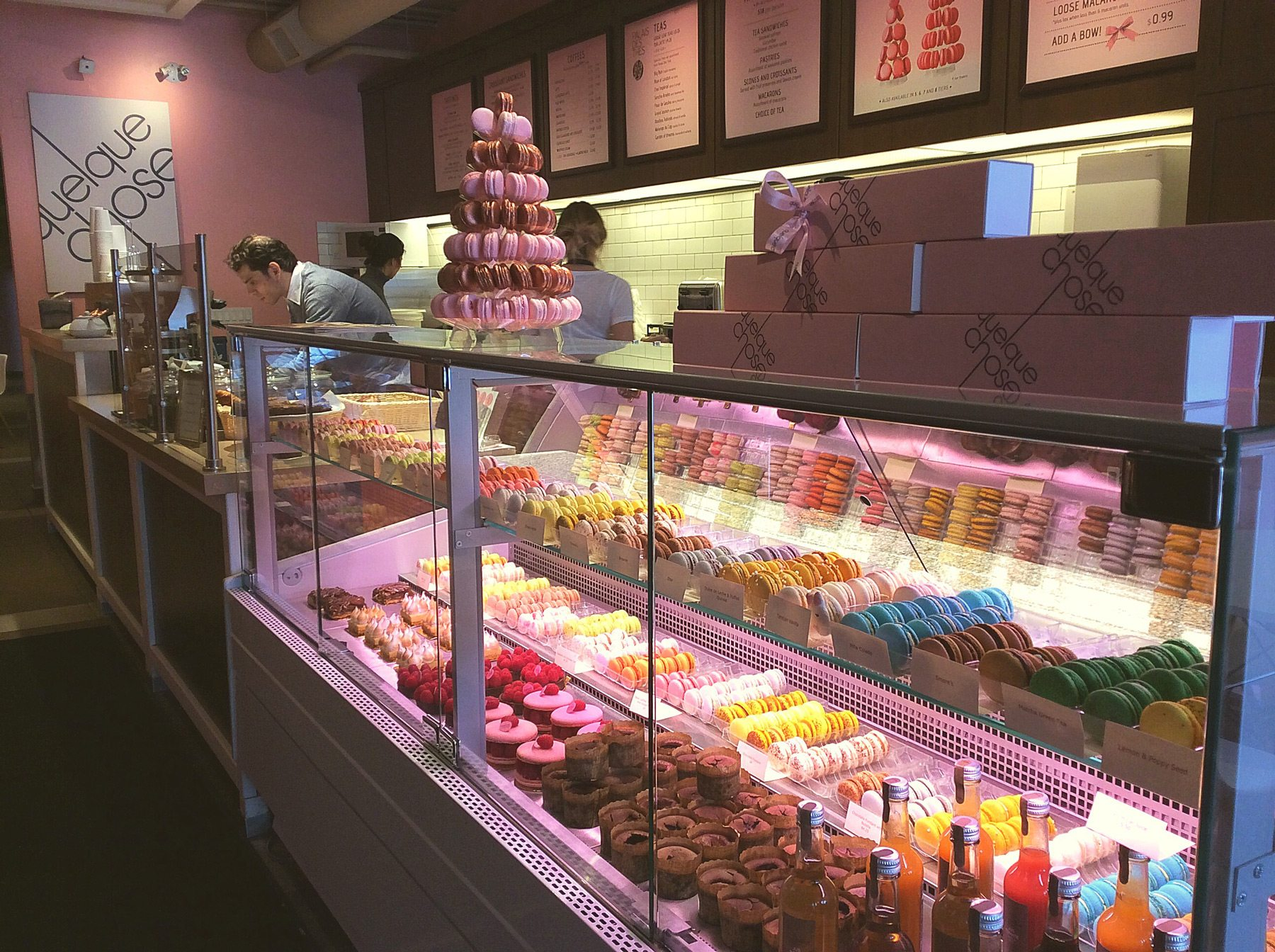 A display case showcases two dozen flavours of macarons and assorted pastries. The shop also sells coffees, teas, and other drinks