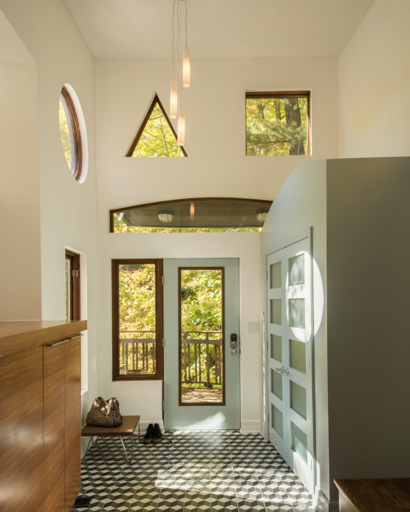 The front hallway is all shapes and angles, with a quirky arrangement of windows allowing light to flood in, illuminating the Escher-inspired tiles. The owner and the designer spent much time discussing whether the tiles should be laid angled or straight. Photography PhotoluxStudio.com — Christian Lalonde
