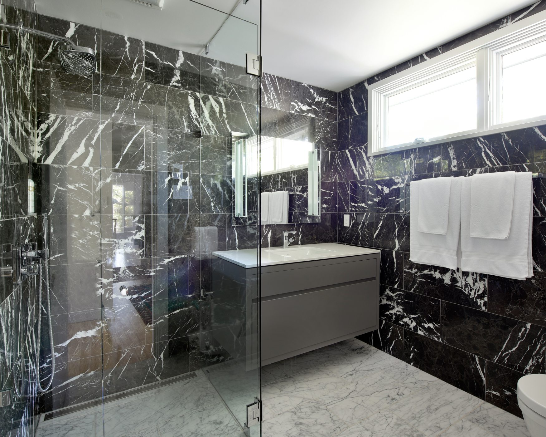 The Willcoxes collaborated with Deslaurier Custom Cabinets on this unique master bathroom encased in two types of marble. They wanted the shower to be designed without a threshold, so the stall floor slopes about three-quarters of an inch to allow the water to drain on the wall side. Photos: Gordon King