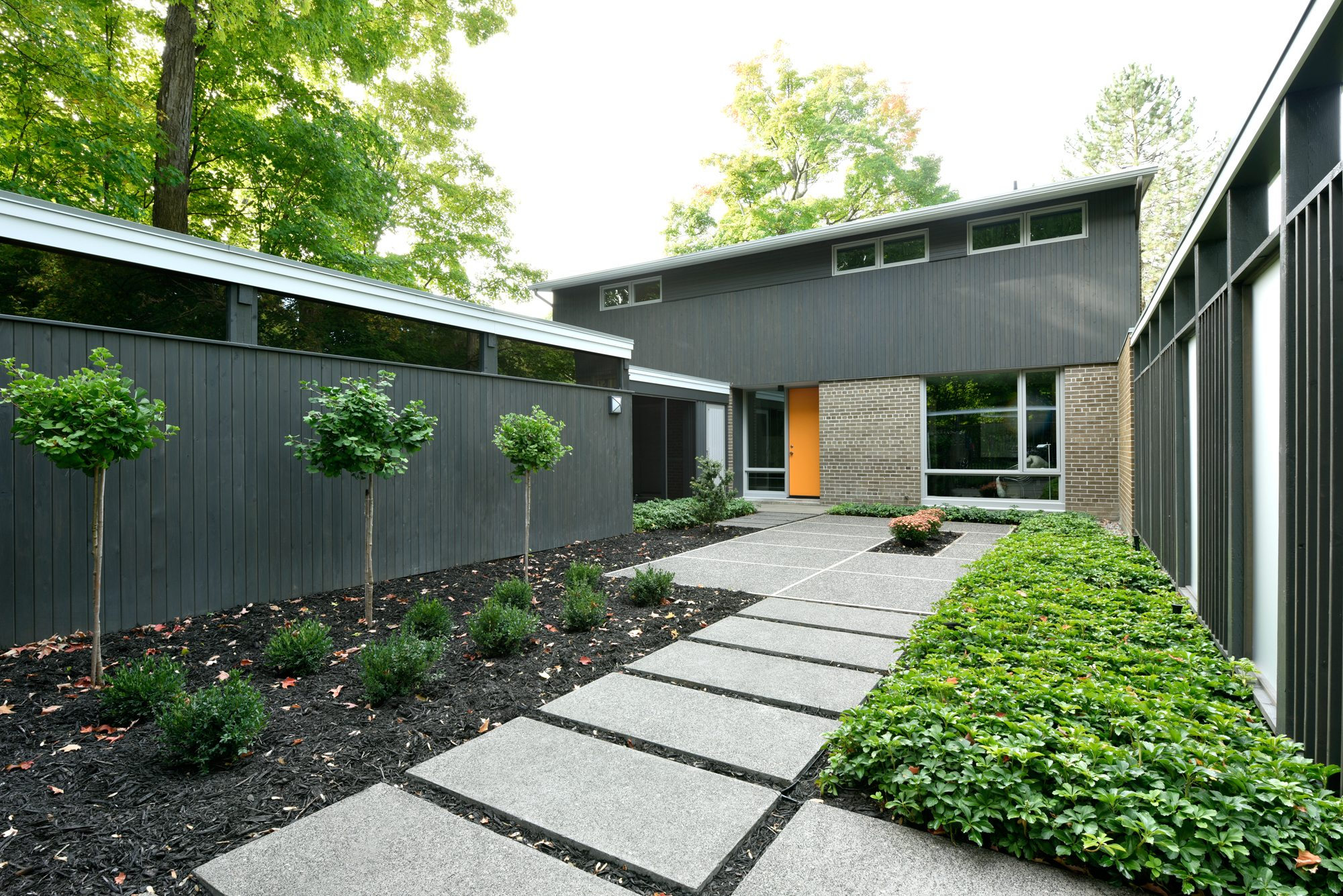Above left The woodwork in the inner courtyard was transformed from dull brown to warm grey, translucent panels were installed in the fence, and the garden was simplified to present a modern entryway to the house. Photos: Gordon King