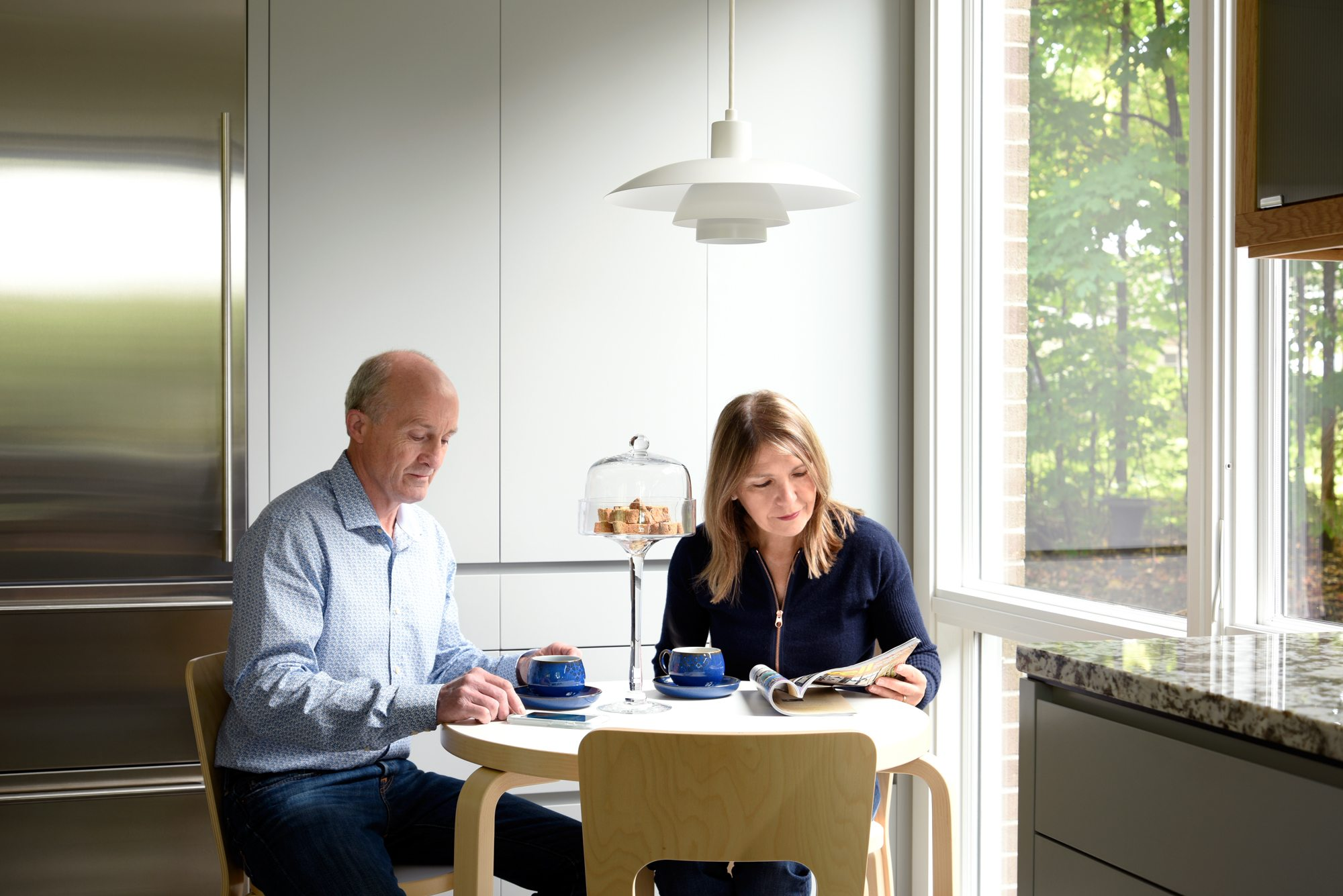 Despite the forested setting, sun floods many rooms, including the kitchen eating nook where the Willcoxes enjoy a rare moment of relaxation. Photos: Gordon King
