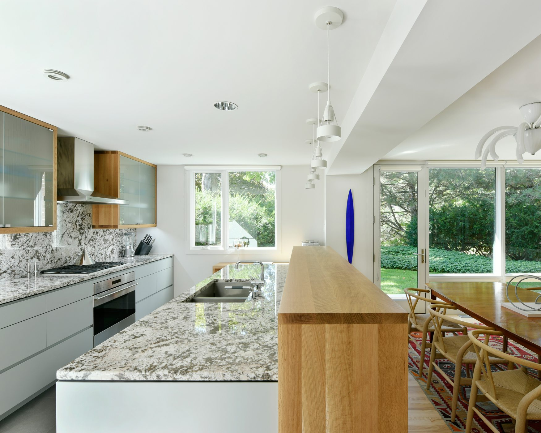 The former kitchen was completely reconfigured: walls and headers were torn down, and a modern kitchen with ample storage and a showpiece island was custom-built by Deslaurier Custom Cabinets. The marble is Bianco Antico from Brazil. Photos: Gordon King
