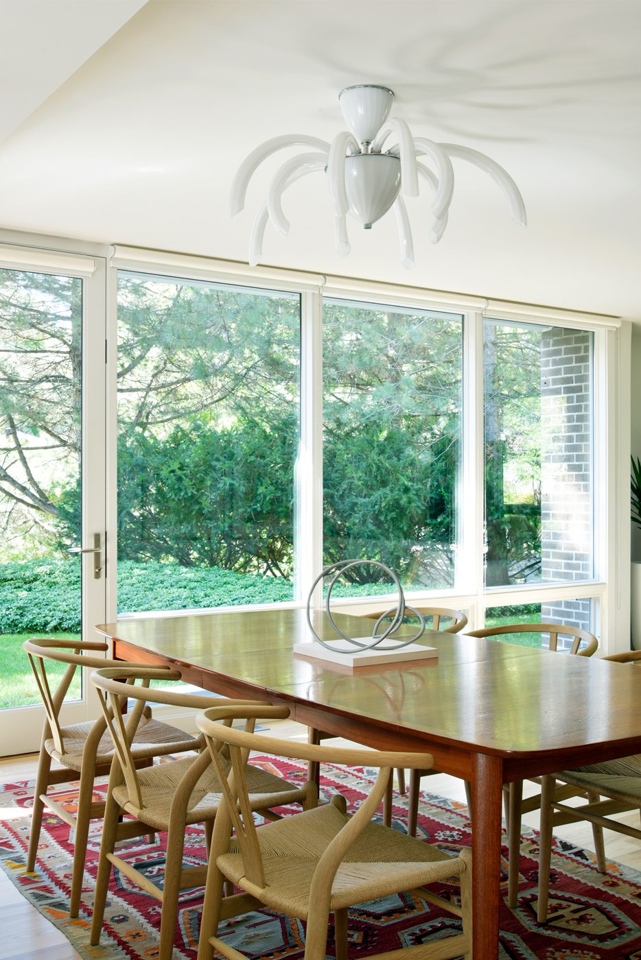 "In keeping with the vintage of the house, the Willcoxes sourced Hans Wegner Wishbone chairs  for their dining room. ""They're like a little piece of sculpture,"" says Debbie. The teak dining table was original to the house and purchased from the family, while the light fixture is Murano glass. Photos: Gordon King"