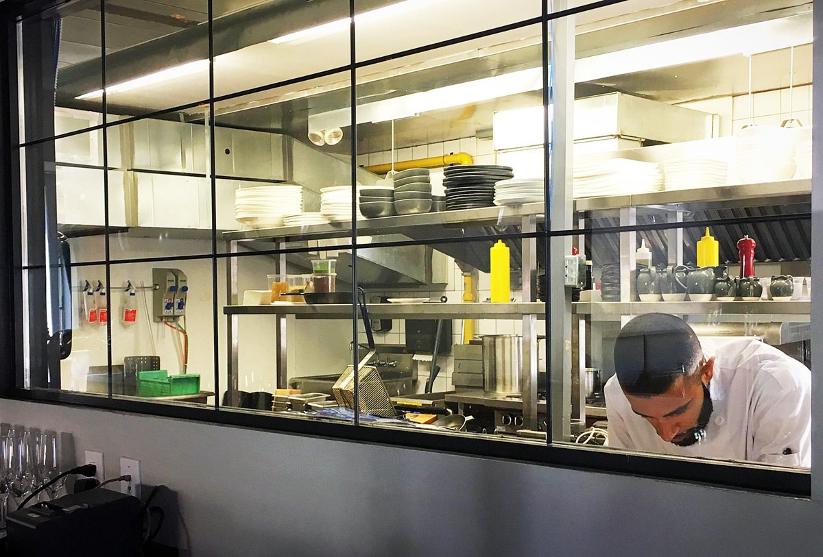A window at the back of the restaurant offers a peek into the kitchen, where sous-chef Imrun Texeira preps for opening night