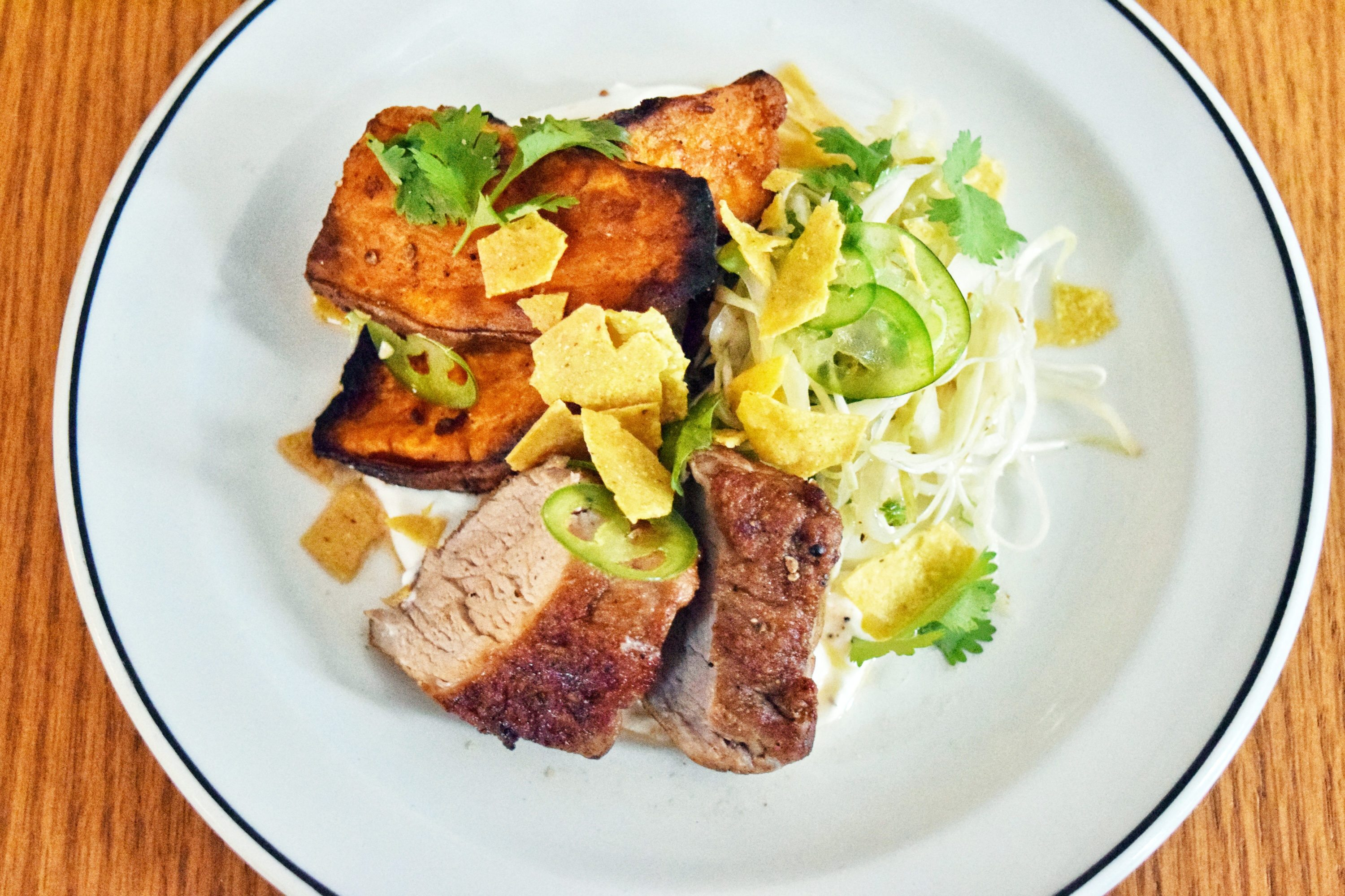 The Third's compact menu includes a pork tenderloin dish served with paprika cabbage slaw, sweet potatoes, sour cream, and cilantro