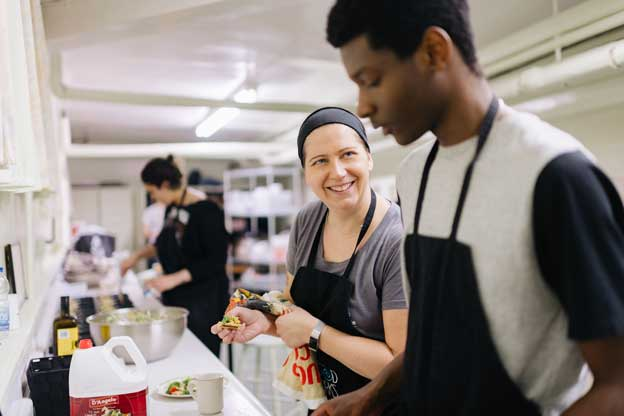 "Julie Cugalj, a government policy analyst, volunteers with FoodWorks. ""It's a very empowering environment,"" she says, explaining that the young participants gain confidence as their kitchen skills improve. ""I've seen people come in and be quickly transformed"". Photo: Ben Welland"