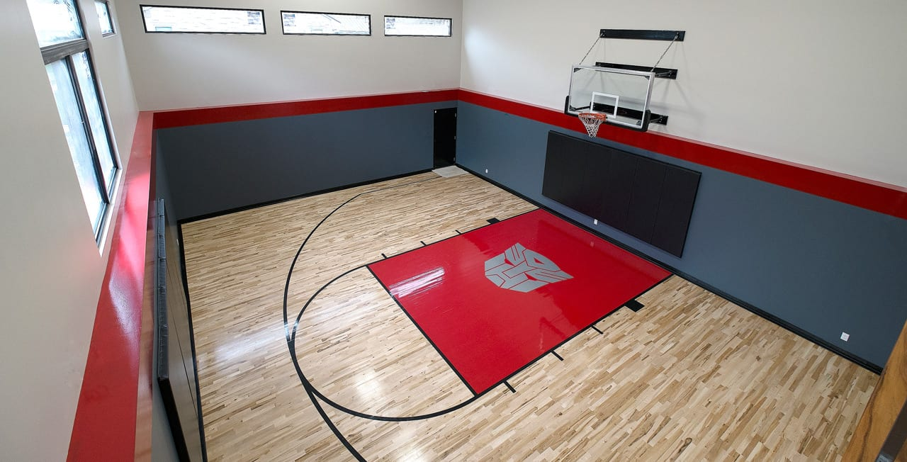 While the owner hits the court at least three nights a week for basketball with friends, his sons take a wider-ranging view of what the room's all about, hosting dodgeball and floor hockey games or surfing their hoverboards. It took two days and multiple layers of paint to get the Transformers logo just right. A viewing gallery (far right) allows spectators a vantage point to watch the game. Photo: Christos Spentzos